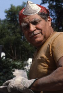 A man with a dust mask and red bandana looks into the camera